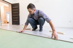 Άτομο εργαζομένων ξυλουργών που εγκαθιστά τον ξύλινο πίνακα παρκέ κατά τη διάρκεια της εργασίας δαπέδων με το σφυρί στοκ εικόνες με δικαίωμα ελεύθερης χρήσης