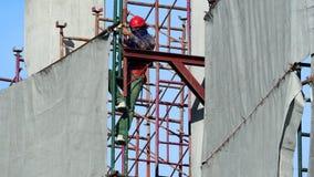Άτομο εργασίας που εργάζεται στο εργοτάξιο οικοδομής με το κράνος Στοκ φωτογραφία με δικαίωμα ελεύθερης χρήσης