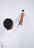 Άτομο ζωγράφων στην εργασία με μια ζωγραφική βουρτσών στον τοίχο Στοκ Εικόνες