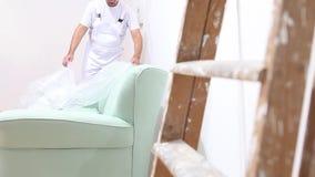 Άτομο ζωγράφων στην εργασία με τον πλαστικό tarp στον καναπέ και τη σκάλα που κλίνουν ενάντια στον τοίχο απόθεμα βίντεο