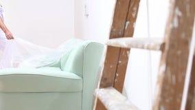 Άτομο ζωγράφων στην εργασία με τον πλαστικό tarp στον καναπέ και τη σκάλα που κλίνουν ενάντια στον τοίχο φιλμ μικρού μήκους