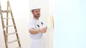 Άτομο ζωγράφων στην εργασία, με τον τοίχο ζωγραφικής κυλίνδρων, σπίτι ζωγράφων απόθεμα βίντεο