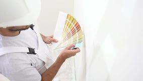 Άτομο ζωγράφων στο χρώμα επιλογής εργασίας με swatches τα δείγματα, έννοια ζωγραφικής τοίχων, άσπρο διάστημα αντιγράφων φιλμ μικρού μήκους