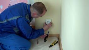 Άτομο ηλεκτρολόγων με την τάση δοκιμής δεικτών κατσαβιδιών στην υποδοχή εξόδου φιλμ μικρού μήκους