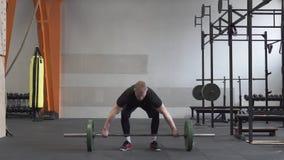 Άτομο ικανότητας που κάνει barbell την άσκηση αρπαγής στη γυμναστική φιλμ μικρού μήκους