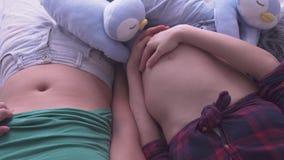 Άτομο και έγκυος γυναίκα που βρίσκονται στο κρεβάτι με τα γυμνά tummies Προσοχή αναμενουσών μητέρων Έννοια μητρότητας Εγκυμοσύνη  απόθεμα βίντεο
