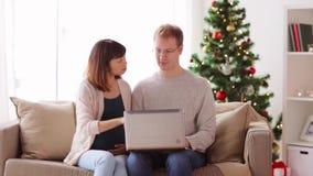 Άτομο και έγκυος σύζυγος με το lap-top στα Χριστούγεννα φιλμ μικρού μήκους