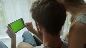 Άτομο και η φίλη του που χρησιμοποιούν την ταμπλέτα πράσινη οθόνη μεγάλη για το πρότυπο, οι περισσότερες δημοφιλείς χειρονομίες χ φιλμ μικρού μήκους