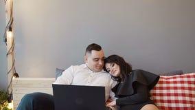 Άτομο και η όμορφη έγκυος σύζυγός του που χρησιμοποιούν το lap-top τους στο κρεβάτι τους στο σπίτι Ευτυχής οικογένεια, πρόσωπο 2 φιλμ μικρού μήκους