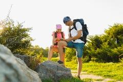 Άτομο και κορίτσι με το σακίδιο πλάτης που στηρίζεται και που εξετάζει το χάρτη Στοκ Εικόνες