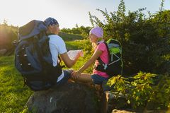 Άτομο και κορίτσι με το σακίδιο πλάτης που στηρίζεται και που εξετάζει το χάρτη Στοκ Φωτογραφίες
