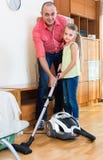 Άτομο και μικρό κορίτσι που σκουπίζουν με ηλεκτρική σκούπα στο σπίτι Στοκ εικόνες με δικαίωμα ελεύθερης χρήσης