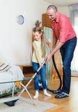 Άτομο και μικρό κορίτσι που σκουπίζουν με ηλεκτρική σκούπα στο σπίτι Στοκ Εικόνες