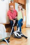 Άτομο και μικρό κορίτσι που σκουπίζουν με ηλεκτρική σκούπα στο σπίτι Στοκ Φωτογραφία