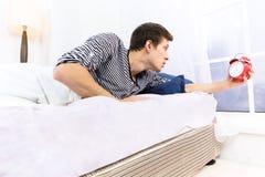 Άτομο και ξυπνητήρι στο κρεβάτι Στοκ φωτογραφία με δικαίωμα ελεύθερης χρήσης