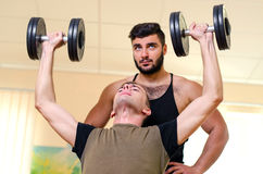 Άτομο και ο προσωπικός εκπαιδευτής του που ασκούν με τους αλτήρες στη γυμναστική Ασκήσεις τεχνικής για τους ώμους αθλητής αρχαρίω Στοκ φωτογραφία με δικαίωμα ελεύθερης χρήσης