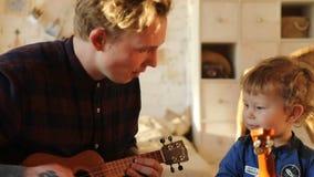 Άτομο και παιδί που παίζουν ukulele απόθεμα βίντεο