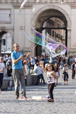 Άτομο και παιδί μικρών κοριτσιών με τις μεγάλες φυσαλίδες σαπουνιών Στοκ Φωτογραφίες