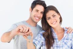 Άτομο και σύζυγος που κρατούν ένα κλειδί με ένα σπίτι keychain Στοκ Φωτογραφία