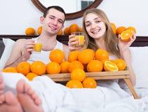 Άτομο και φίλη που πίνουν το συμπιεσμένο χυμό από πορτοκάλι στο κρεβάτι Στοκ φωτογραφίες με δικαίωμα ελεύθερης χρήσης
