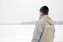 Άτομο κοντά στον παγωμένο ποταμό το χειμώνα Στοκ Φωτογραφίες