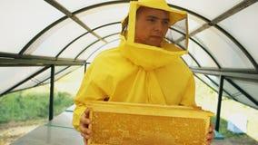 Άτομο μελισσοκόμων που περπατά με τα ξύλινα πλαίσια που λειτουργούν στο μελισσουργείο Στοκ εικόνα με δικαίωμα ελεύθερης χρήσης