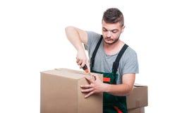 Άτομο μετακινούμενων που χρησιμοποιεί το εργαλείο κοπτών στα κουτιά από χαρτόνι Στοκ Φωτογραφία