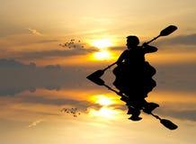 Άτομο με ένα καγιάκ στο ηλιοβασίλεμα απεικόνιση αποθεμάτων