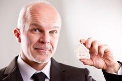 Άτομο με ένα μικρό σπίτι στο χέρι του που εξετάζει σας Στοκ φωτογραφίες με δικαίωμα ελεύθερης χρήσης