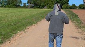 Άτομο με ένα τηλέφωνο ράβδων και κυττάρων αλιείας στο δρόμο απόθεμα βίντεο