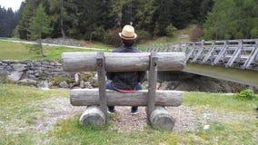 Άτομο με ένα sittin καπέλων στον πάγκο σε ένα ελβετικό βουνό Στοκ Φωτογραφία