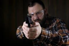 Άτομο με βαλμένος στα προστατευτικά προστατευτικά δίοπτρα και την κατάρτιση αυτιών στο πιστόλι SH Στοκ εικόνα με δικαίωμα ελεύθερης χρήσης