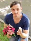 Άτομο με μια ανθοδέσμη των τριαντάφυλλων και ενός δαχτυλιδιού διαμαντιών Στοκ Εικόνες
