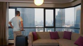 Άτομο με μια βαλίτσα στο υπόβαθρο των ουρανοξυστών σε ένα πανοραμικό παράθυρο στοκ εικόνες με δικαίωμα ελεύθερης χρήσης