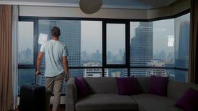 Άτομο με μια βαλίτσα στο υπόβαθρο των ουρανοξυστών σε ένα πανοραμικό παράθυρο στοκ φωτογραφίες με δικαίωμα ελεύθερης χρήσης