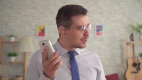 Άτομο με μια ενίσχυση ακρόασης στο αυτί του στο καθιστικό που μιλά σε ένα smartphone φιλμ μικρού μήκους