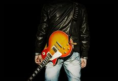 Άτομο με μια κιθάρα στον ώμο του που απομονώνεται στο μαύρο υπόβαθρο στοκ εικόνες με δικαίωμα ελεύθερης χρήσης
