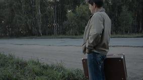Άτομο με μια παλαιά βαλίτσα που υπερασπίζεται το δασικό δρόμο φιλμ μικρού μήκους