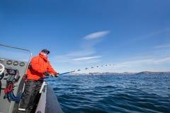 Άτομο με μια ράβδο αλιείας στα χέρια του Κόκκινο σακάκι Αθλητικά γυαλιά στοκ φωτογραφία με δικαίωμα ελεύθερης χρήσης