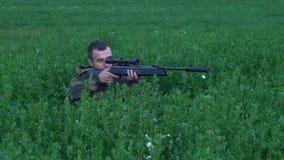 Άτομο με μια συνεδρίαση πυροβόλων όπλων στην ψηλή χλόη 4k φιλμ μικρού μήκους