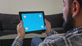 Άτομο με μια ψηφιακή ταμπλέτα με την μπλε κίνηση οθόνης απόθεμα βίντεο