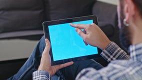 Άτομο με μια ψηφιακή ταμπλέτα με την μπλε οθόνη απόθεμα βίντεο