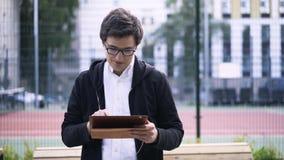 Άτομο με τα ακουστικά και μια ταμπλέτα κοντά σε ένα γήπεδο αντισφαίρισης απόθεμα βίντεο