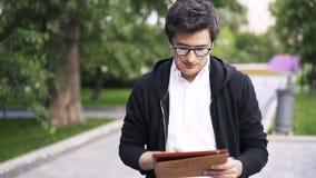 Άτομο με τα ακουστικά και μια ταμπλέτα που περπατά σε ένα πάρκο απόθεμα βίντεο