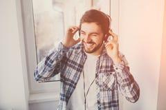 Άτομο με τα ακουστικά που χαμογελούν και που ακούνε τη μουσική στοκ εικόνα
