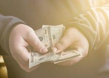 Άτομο με τα αμερικανικά δολάρια χρημάτων στα χέρια Αρσενικά τέμνοντα μετρητά Εκλεκτής ποιότητας αναδρομικός ύφους που τονίζεται Στοκ εικόνες με δικαίωμα ελεύθερης χρήσης