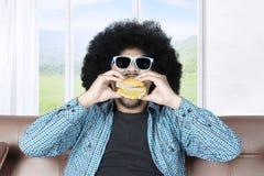Άτομο με τα γυαλιά ηλίου που απολαμβάνει cheeseburger Στοκ εικόνα με δικαίωμα ελεύθερης χρήσης