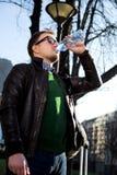 Άτομο με τα γυαλιά που στέκονται στο πάρκο, πόσιμο νερό από ένα BOT στοκ φωτογραφία με δικαίωμα ελεύθερης χρήσης