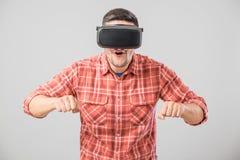 Άτομο με τα γυαλιά εικονικής πραγματικότητας που πληρώνει τον προσομοιωτή ποδηλάτων Στοκ Φωτογραφίες