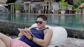 Άτομο με τα γυαλιά ηλίου που κάθεται από τη λίμνη με την ψηφιακή ταμπλέτα στο τροπικό θέρετρο απόθεμα βίντεο